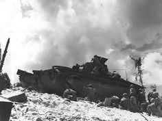 Using an Amtrac as shelter, American Marines fought on the beaches of Peleliu, Palau Islands, 15 Sep 1944