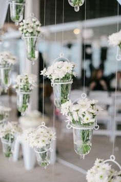 Hanging white flowers. We incorporate this often. Sometimes lighting happens best from other parts of a space but you still want to bring a ceiling height down or create a wall of sorts with something hanging. And you can also choose to alternate, some flowers some candles.