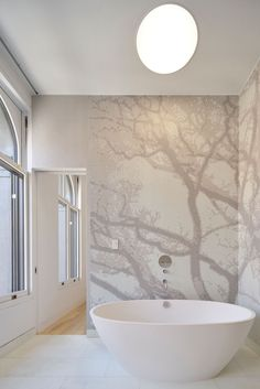 This renovated bathroom has a standalone tub surrounded by tile mural.