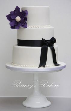 wedding cake, simple and elegant white, black ribbon with a blue flower instead of purple with a Mr & Mrs Goforth topper!