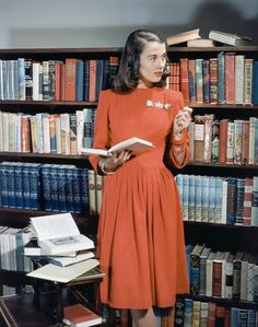 Model in red dress of rabbit's wool, cut with dirndl lines, standing near bookshelves,1941.