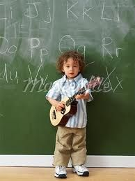 Omg it's a ukulele but he's so small it looks like a guitar