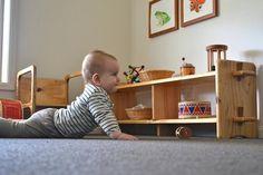 Le nido (espace de jeu Montessori) - Une petite étagère basse, sur la longueur, laisse à portée de l'enfant quelques jouets. Ça favorise son autonomie. Il est préférable, selon l'approche Montessori, de faire une rotation des jouets et d'en présenter que quelques-uns à la fois.