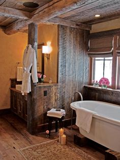 HGTV presents a rustic barn-style bathroom with soaking tub, exposed ceiling beams, and wooden floor, ceiling and walls plus modern amenities.