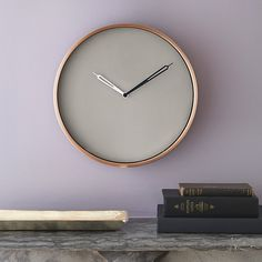 ahead of it's time. Rimmed in a shiny circle of rose gold, this gleaming aluminum wall clock is perfectly timed with the trend. Sophisticated quartz movement tells time on a clean grey face while two-color hands tick away the minutes. Elevates the entry or goes glam grouped on a gallery wall. Requires two AA batteries (not included).