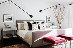Bedroom with industrial wall sconces, feminine blush tones, and a vintage Persian rug