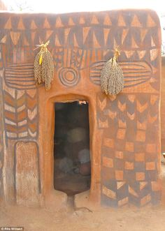 African scenes: Dried plants hang above the entrance to one of the huts in the village