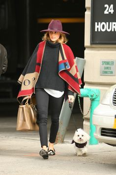 Olivia Palermo in a Burberry monogrammed blanket cape + black sweater + white tee + black jeans + wide-brim fedora