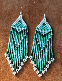 Ivory Green Turquoise native beaded earrings hang in your choice of 3, 4 or 7 long in a beautiful and unique design. You can also choose from Hypo allergenic, silver plated or rose gold plated ear wires. Hand made by Suzanne Flumerfelt in Yukon, Canada.