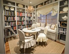 bookshelves with built-in window seat, small round table with 2 chairs for cozy study space.