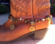 Dress up your cowboy boots or any pair of boots for that matter with this boot jewelry. Its adjustable and should fit about any type of boot. Two of the pendants have crystals in them, and there is just the right amount of bling. The brass tones should match almost any pair of boots. Made with glass seed beads, crystals, glass painted mother of pearl and metal pendants.