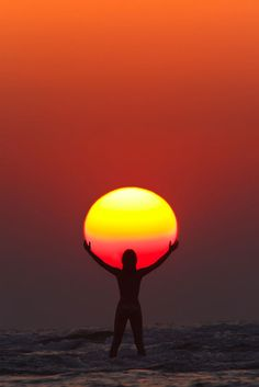 Photograph by Anton Jankovoy | jankovoy.com   In this perfectly timed sunset capture by Anton Jankovoy, we see the silhouette of a woman appearing to hold/praise the sun. The photo was taken in July of 2011 at Paradise Beach in Maharashtra, India. To get the shot Anton used a FL 600mm at 1/250 sec, f/11, ISO 200.