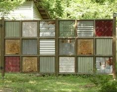 I love this look using old tins for a privacy fence.