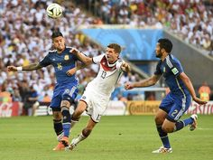 Germany's Thomas Mueller (C) fights for the ball with Argentina's Marcos Rojo and Ezequiel Garay (R) during their 2014 World Cup final at the Maracana stadium in Rio de Janeiro July 13, 2014.