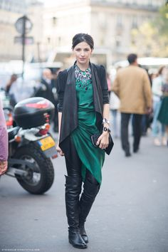 Catalina in an emerald green rhinestone statement necklace, green silk drape dress, and over-the-knee black leather boots.