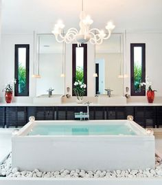 modern-bathroom-with-elegant-decoration-equipped-with-standalone-bathtub-beautiful-chandelier-twin-mirrors-and-twin-basins-with-modern-fauce...