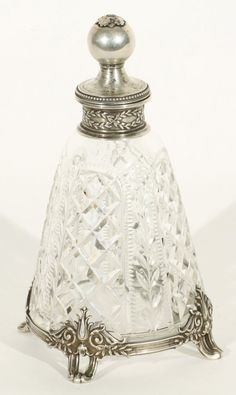 A CUT GLASS AND SILVER PERFUME BOTTLE, BOLIN, MOSCOW, 1899-1908, the tapered cylindrical body with cut glass panels of floral and geometric ornament, silver mounted on four feet, the stopper with a ball-shaped finial