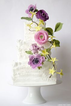 A soft and frilly wedding cake design perfect for summer. Featuring lush sugar flowers in shades of pink and purple. Created by Lemon Tree Cakes.