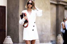Candela Novembre wears a white mini dress with black buttons, a shoulder bag, and black sunglasses
