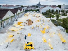located in cognac, france, the undulating and iridescent structure is designed to host visitors and events underneath.