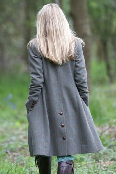 wearing a gorgeous grey coat with riding boots.