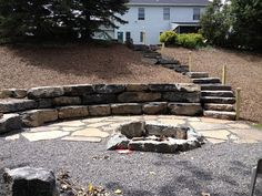 I know that in a lot of houses that have a large slope in their back yards, it is often hard to think of something to do with the space.  I think adding some stairs and a fire pit is a great way to make use of the hill and the space in the back yard.  Putting in a fire pit not only uses the available space but it also adds a nice place to have friends over and to talk late into the night.