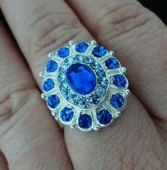 Belíssimo anel prata regulável cravejado com strass e pedras swarovski azul royal. 1,8 cm. Ref. A381.