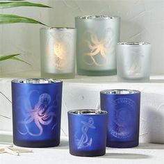 Two's Company Aegean Sea Set Of 3 Tealight Candleholders. Aegean Sea Set of 3 Silhouette Frosted Tealight Candle Holders Includes 3 Sizes/Designs Assorted 2 Colors: Small/Anchor, Medium/Spiral Shell, Large/Octopus in Silver and Navy - Glass
