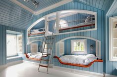 Nautical boys' bedroom with blue wood paneled walls, built-in bunk beds pods, and vaulted ceiling
