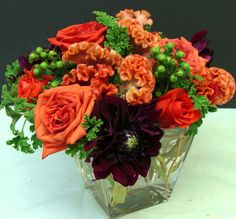 This is a cube vase floral arrangement that features roses, coxcomb and dahlias in an orange and burgundy color scheme.  See our entire selection at www.starflor.com.  To purchase any of our floral selections, as gifts or décor, please call us at 800.520.8999 or visit our e-commerce portal at www.Starbrightnyc.com. This composition of flowers is generally available for same day delivery in New York City (NYC). SQ102