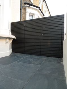 LM - bin store in contemporary slats to match side panel adjacent to no 9. include bin cover/area. Top of bike store to be just shorter than no 13 and same level/no higher than top of metal railings