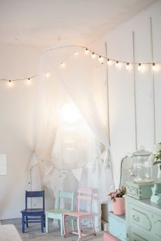 love the ethereal feel of this space ~ perfect for the imaginings of little ones. the painted chairs with soft colors against the white backdrop, the flowing canopy to create a magical hideaway in the corner & those gorgeous lights (really like that larger size bulb)