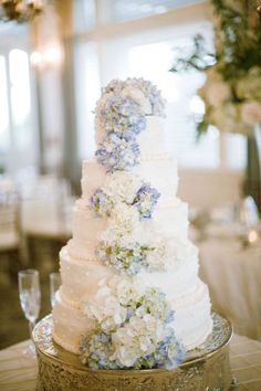 Romantic confection decorated with a lush cascade of white and pale blue hydrangeas. #wedding #cake #hydrangea