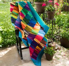 """Paper piece your way to perfection with the Reflections Quilt Kit! You'll receive a paper-piecing pattern and beautiful Benartex Gradations fabric to sew this stunning, 56"""" x 63"""" quilt top. Featuring gradated fabrics and an array of vivid hues, this daring design will catch your eye and win your heart."""