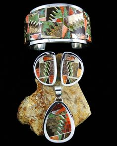 Cuff, earrings and pendant | Tommy Jackson (Navajo). Sterling silver with an Navajo rug pattern inlay made by combining natural Royston turquoise, picture jasper, brown opal, serpentine and spiny oyster.