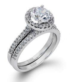Round diamonds, 0.46tw, are set into a white gold, cathedral mounting featuring a halo. The matching wedding band is also prong set with diamonds.