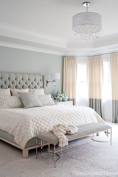 A modern and glamorous Greenwich home with a beautiful master bedroom. A chandelier, upholstered headboard, wall sconces and nightstands in white, blue and silver are always chic.