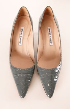 "Manolo Blahnik Grey Patent Spectator Heels - A dainty kitten heel in a subtle neutral that can carry you from season to season. This comfortable pointed pump features a perforated laser-cut spectator design, making these sophisticated and feminine. Material(s): Patent Leather Heel Height: Low (1 - 2"")"