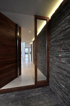 Textured front entrance with an amazing floor to ceiling, heavy wooden front door