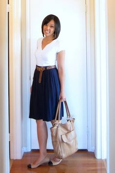 White v-neck top, navy skirt, brown shoes with beige back and brown belt.