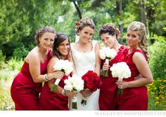 White dress offset by red flowers for the bride, and the reverse for the bridesmaids.