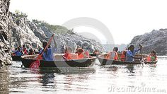 Several tourist families on a coracle ride in the deep canyons  though which Cauvery River flows,  at Hogenakkal Falls, Tamil Nadu.
