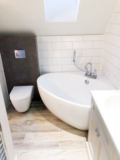 A contemporary rounded bathtub fits snugly in the corner of this compact loft bathroom. Natural light floods into the bathroom from the bold skylight on the loft's slanted ceiling. Small Corner Bath, Small Attic Bathroom, Small Bathroom Layout, Compact Bathroom, Small Bathtub, Loft Bathroom, Small Laundry Rooms, Upstairs Bathrooms, Corner Tub