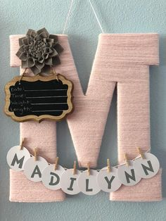 A 13.5 wooden letter wrapped twice in soft acrylic yarn with flower embellishment. (Shown in picture is soft pink acrylic yarn with gray dahlia flower) Letter is perfect to hang on hospital door for baby birth announcement attached on letter is a small chalkboard with date, time,