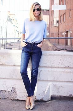 A blue t-shirt is tucked into blue skinny jeans, worn with nude heels, and aviator sunglasses