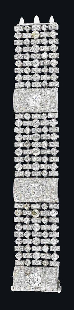 AN ART DECO DIAMOND BRACELET, BY BULGARI   Designed as a wide mesh band of alternated circular-cut diamonds and rectangular-shaped diamond-set links, enhanced by three pavé-set diamond bombé spacers, centering upon two cushion-shaped and one circular-cut diamonds, mounted in platinum, late 1930s, 19.4 cm  Signed Bulgari