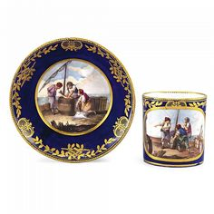 A SÈVRES CUP AND SAUCER 1764 gobelet litron et soucoupe  of the first size, decorated with a blue ground reserved with fishermen in harbour scenes painted by Morin, the ground richly gilded with laurel branches  Quantity: 2 interlaced Ls enclosing dateletter L for 1764, painter's mark M for Jean-Louis Morin, saucer with incised reversed S, cup with oo and another indistinct mark possibly uo cup 7.6cm., 3in., saucer 13.9cm.,5.½in.