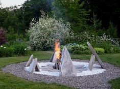 Dan Snow's lit fire sculpture at twilight in the center of the informal perennial garden and mixed borders leading to the potager ⓒ Michaela at TGE
