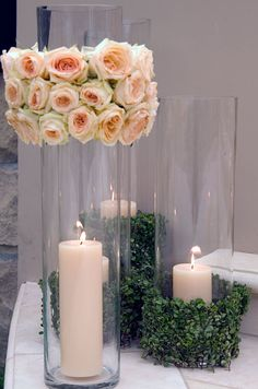 Votive candles are decorated with greenery and light pink roses. desc