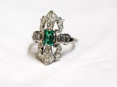 An Enchanting Emerald cut Emerald sparkles in this Vintage Emerald and Diamond Ring